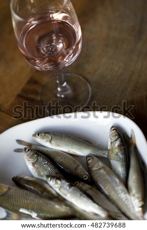 Small fresh fishes on a white plate and rose wine in a glass