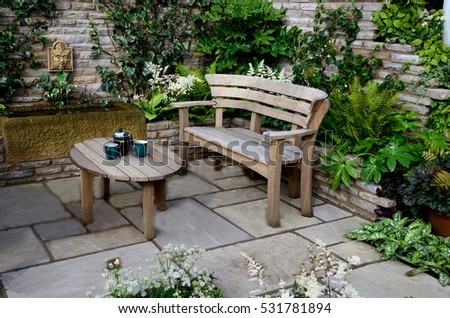 Small garden idea for wooden garden seating and table in a walled patio garden