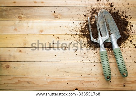 Small gardening shovel and fork on wooden background. - stock photo