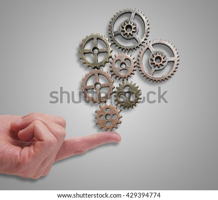 Small gears being balanced on a finger tip