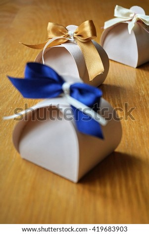 Small gift box made of paper with a colorful ribbon knot atop on a wooden background