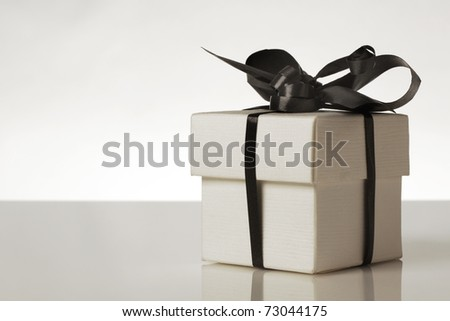 small gift box with a ribbon around the box tied into a bow - stock photo