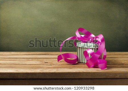 Small gift box with pink ribbon on wooden table - stock photo