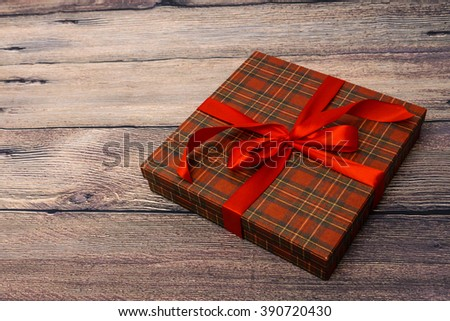 Small gift box with red ribbon on wooden table - stock photo
