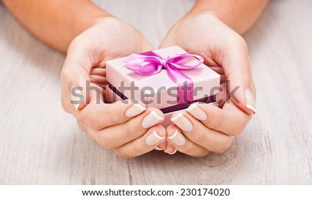 Small gift in female hands close up - stock photo