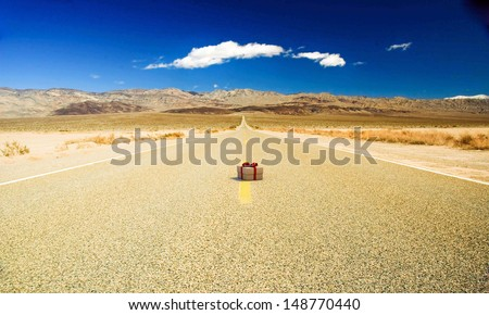 small gift on a desert road - stock photo