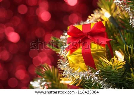 Small gift on Christmas tree.(horizontal) Decorated Christmas tree on red blurry lights background. - stock photo