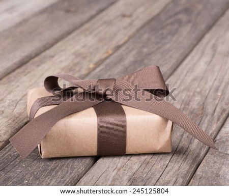 Small gift wrapped in brown paper, ribbon and bow on old boards - stock photo