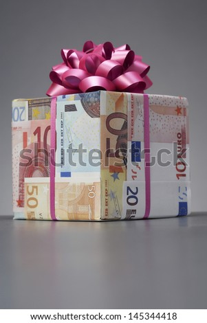 Small gift wrapped in Euro notes with bow - stock photo