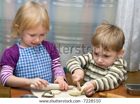 Small girl and boy help on kitchen