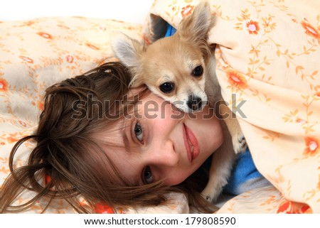 small girl and her chihuahua in the bed - stock photo