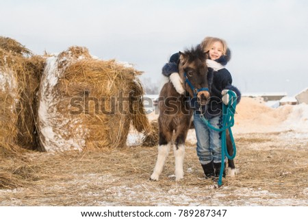 Small girl and small horse in a winter day