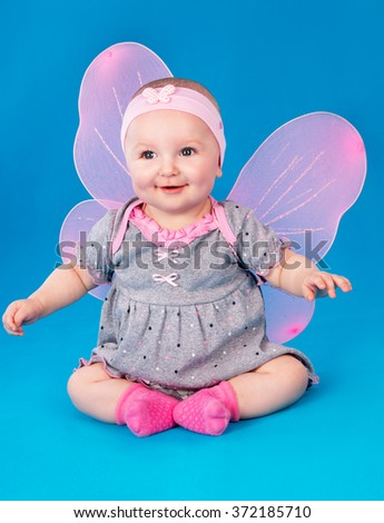 Small girl butterfly wings sitting on the floor on a blue background
