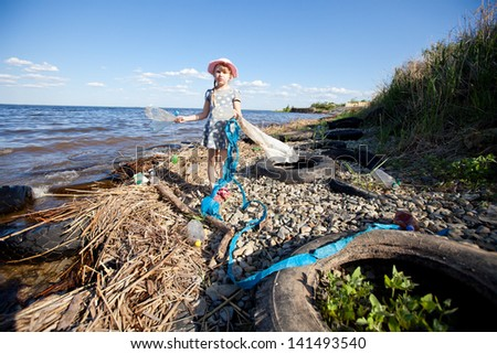 small girl collecting rubbish near the river - stock photo