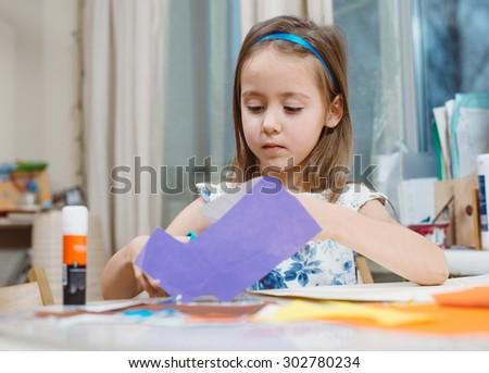 Small girl doing applique - stock photo