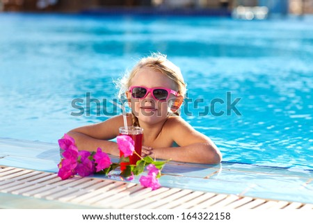 small girl drinking coctail in the pool - stock photo
