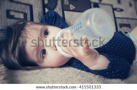 Small girl drinking from a bottle