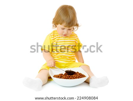 Small girl eat corn flakes isolated on white - stock photo