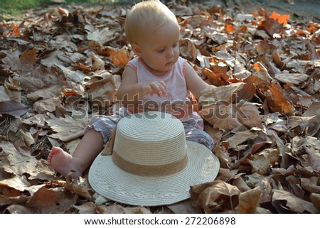 Small girl examining hat and dry leaves - stock photo