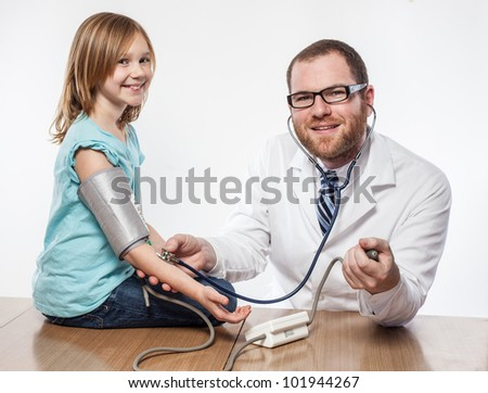 Small girl having her blood pressure tested by male doctor in glasses, young white, blue shirt, modern medicine