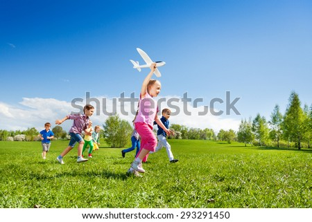 Small girl holds airplane toy and children running - stock photo