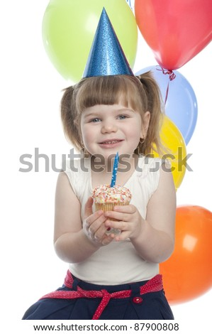 small girl holds up cup cake to show how happy she is.