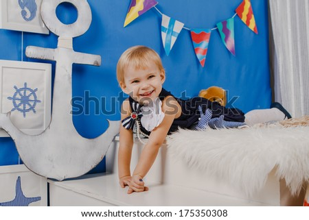Small girl in blue dress laughing and lying on white pelt in photo studio with marine style decoration   - stock photo