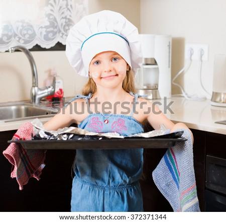 Small girl in cap prepared Italian pizza at home kitchen - stock photo