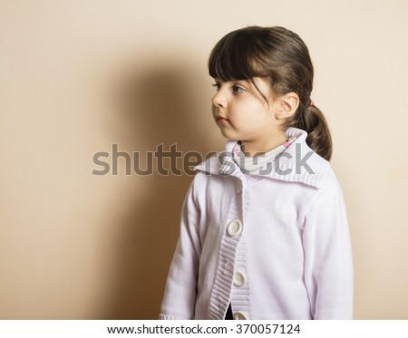 Small girl in studio with off white background - stock photo