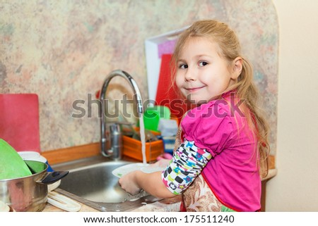 Small girl in the kitchen washing dishes, copyspace - stock photo