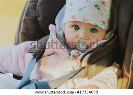 Small girl is sitting in child cat seat, looking at the camera with pacifier - stock photo