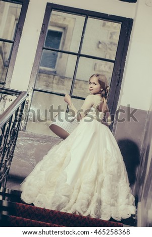 small girl kid with long blonde hair and pretty face in prom princess white dress with basket standing near building glass big window on stairs
