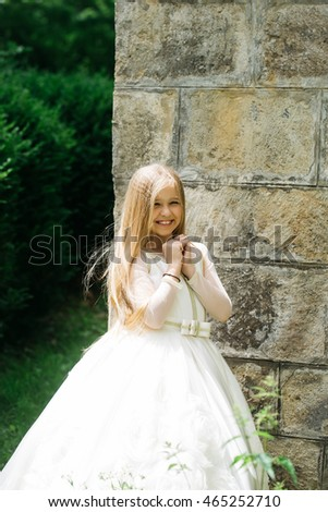 small girl kid with long blonde hair and pretty smiling happy face in prom princess white dress standing in garden with green grass sunny day outdoor