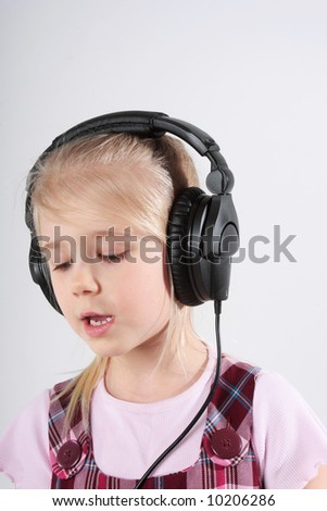 Small girl listening to music on headset