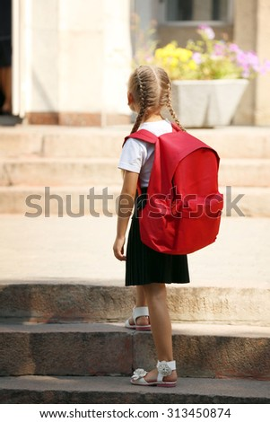 Small girl near school - stock photo