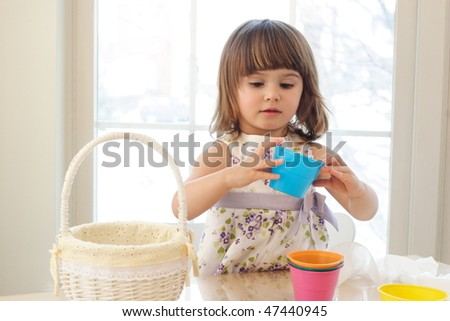 Small girl playing with colorful buckets in a room with a lot of sun light
