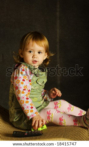 Small girl plays on the armchair