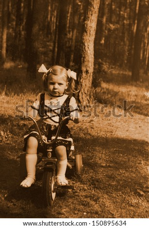 Small girl riding bike in forest - old photography - stock photo