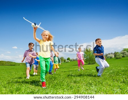 Small girl runs with kids and holds airplane toy