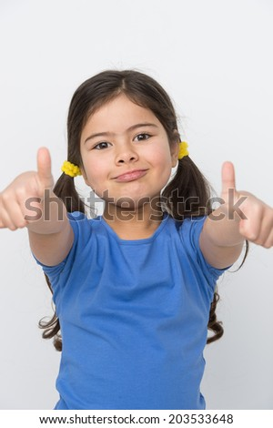 small girl showing two thumbs up. nice girl standing and looking straight - stock photo