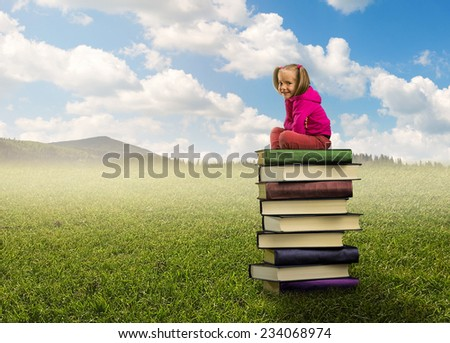 Small girl sits on the pile of books - stock photo