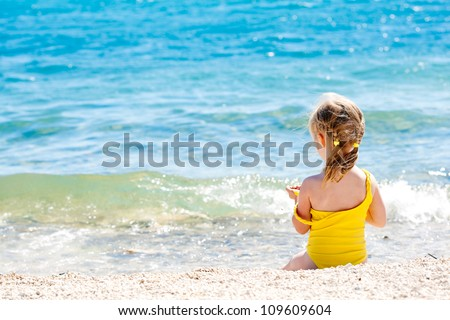 Small girl sitting back on the shore of the sea - stock photo