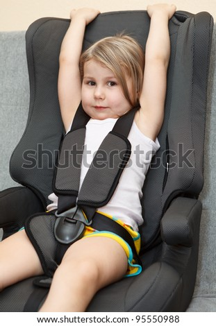 Small girl sitting in a car safety seat with seatbelt - stock photo