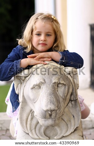 Small girl sitting near sculpture of a lion outdoor