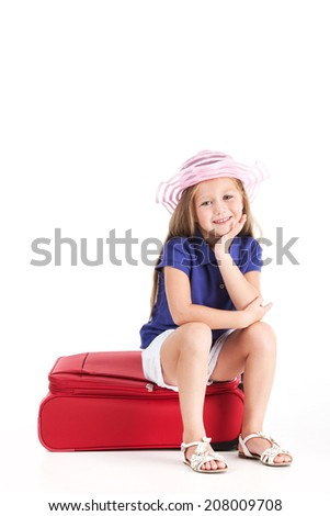 small girl sitting on red bag and smiling. pretty girl in hat and shorts waiting  - stock photo