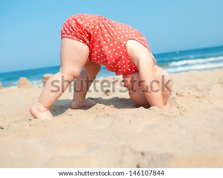 Small girl sitting on sand at beach - stock photo
