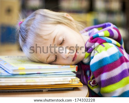 Small girl sleeping on a desk in a classroom - stock photo