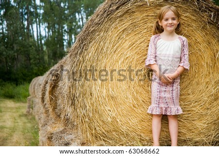 Small girl smiling happily on some hay bales. - stock photo