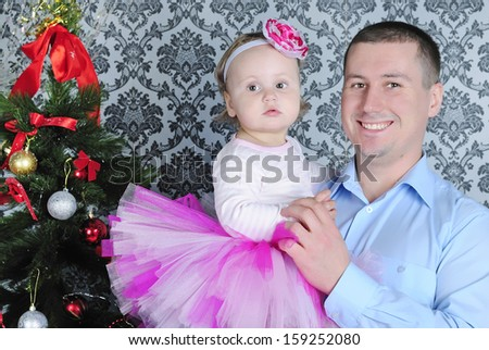 Small girl with father near fir trees