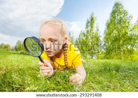 Small girl with magnifier looking through glass - stock photo